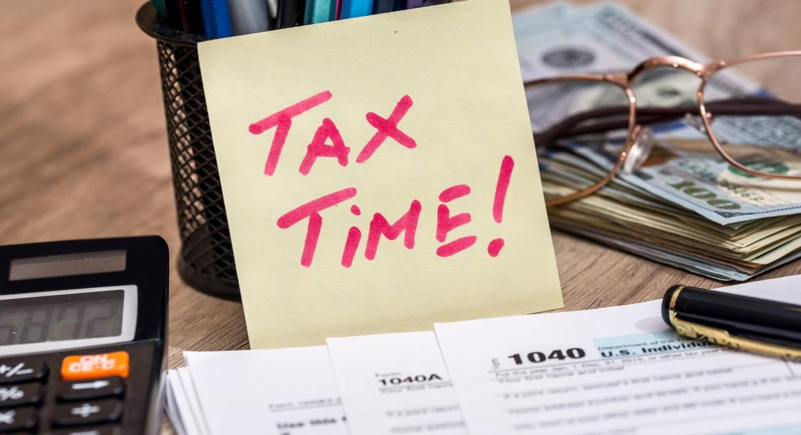 Tax time sticky note with calculator and tax forms